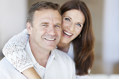Closeup of beautiful woman with arms around her man
